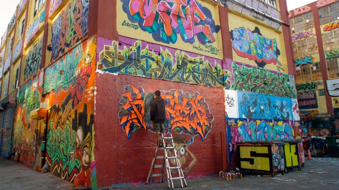 An artist works on his graffiti on the Five Pointz building in Long Island City in Queens in New York